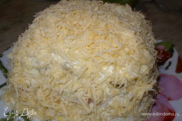 Верх и бока салата покрыть тертым сыром. Украсить, дать настояться час-два в холодильнике.