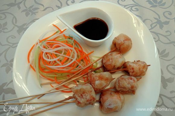 Приготовить легкий гарнир: огурец, морковь и дайкон нарезать тонкой длинной соломкой. Подавать с овощной соломкой и подогретым соусом.