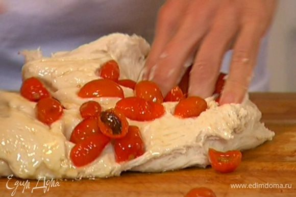 Ножницами сделать в тесте глубокие разрезы и в каждый разрез вставить вяленый помидор и листик базилика.