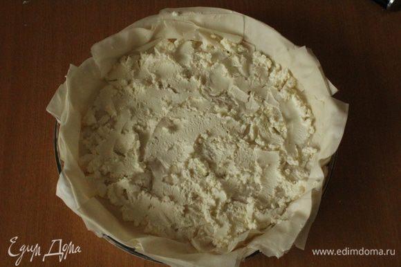 Выстелить смазанную оливковым маслом форму для запекания листьями фило внахлест... Ровным слоем выложить сыр и равномерно его распределить на тесте.