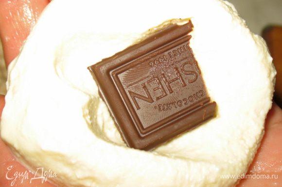 Мокрыми руками формируем сырник, в средину каждого сырника кладем кусочек шоколада и закрываем его другим кусочком творожной массы.
