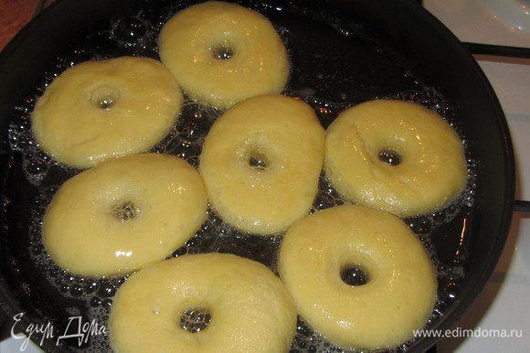 Разогреваем масло на глубокой сковороде или в кастрюле. Масла для жарки должно быть столько, чтобы пончик был погружен наполовину. Очень активно растут во время жарки. Обжариваем пончики до красивого подрумянивания с одной, затем с другой стороны. Обжаренные с двух сторон дрожжевые пончики выкладываем на бумажное полотенце для удаления излишнего масла.