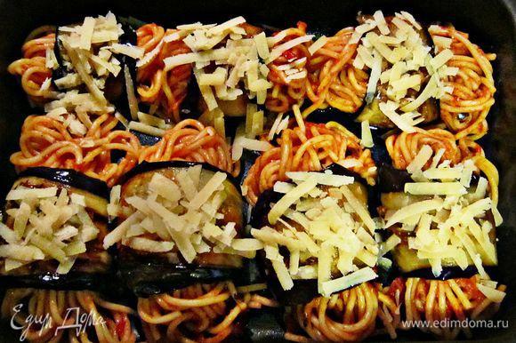 На середину каждого ломтика баклажана выложите немного спагетти и скатайте рулетики. Выложите рулетики на смазанный оливковым маслом противень и сверху посыпьте оставшимся сыром. Запекайте 10 мин при 200г.