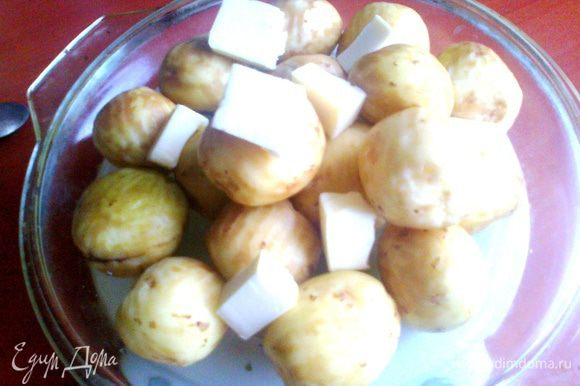 Мелкий картофель (крупный нарезать на четвертинки!) помыть и поскоблить молодую кожицу. Укладываем на тарелку или на крышку от стеклянной формы, как у меня... Сверху хаотично кусочки маслица и соль по вкусу.