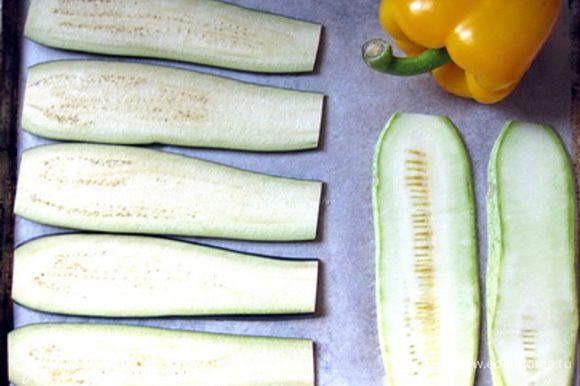 Баклажаны и кабачок нарезать тонкими пластинами вдоль, выложить вместе с целым перцем на застеленный бумагой противень, смазать овощи оливковым маслом.