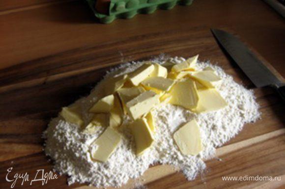 Тесто. Муку высыпать на большую разделочную доску, сверху нарезать крупными кусками маргарин или масло.