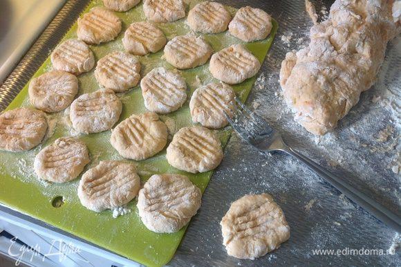 Тесто скатать в колбаски, разрезать на ломтики. Обвалять их в муке и с помощью вилки сделать на ньокках насечки (вилку просто прижать к ломтику). Выложить на поднос и поставить ньокки в холодильник.