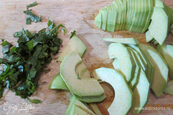 Авокадо очистить от кожуры, удалить косточку, нарезать тонкими ломтиками. Базилик порубить.