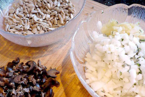Ставим вариться картофель в мундире в небольшом количестве воды до готовности, т.е. минут на двадцать. Разогреваем духовку до 200 градусов. Семечки поджариваем на сухой сковороде. С веточек розмарина снимаем иголочки и мелко рубим их. Лук и оливки режем мелко. Чеснок натираем на мелкой терке.