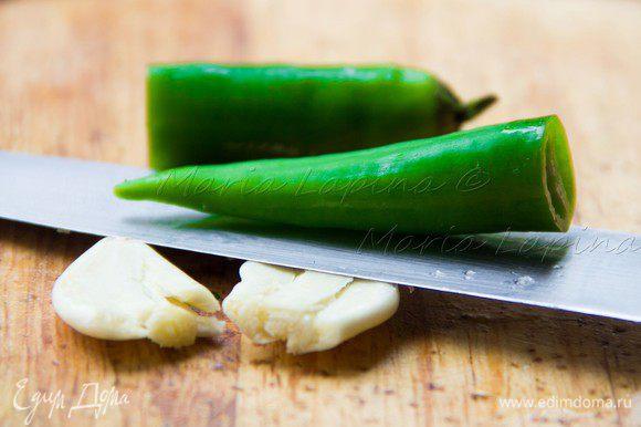 Перец чили разрезать пополам, зубчики чеснока очистить и раздавить плоской стороной ножа.