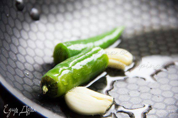 В сковороде разогреть оливковое масло, положить туда перец и чеснок. Обжаривать 3-5 минут, периодически помешивая, затем достать и выбросить. Благодаря этой процедуре у нас получится ароматнейшее, острое чесночное масло для креветок.