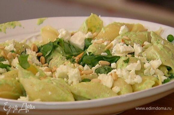 Ракушки выложить на блюдо, порциями вмешать соус, если нужно, добавить немного воды, в которой варились макароны. Посыпать фетой, базиликом и кедровыми орехами, подавать тут же.
