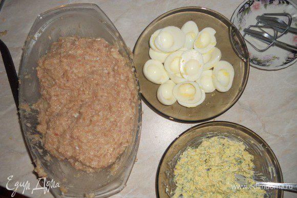 Приготовить фарш. Добавить свежее яйцо, замоченную в молоке мякоть хлеба, соль, перец. Хорошенько перемешать. Варeные яйца почистить и разрезать пополам. Вынуть желток. Натереть на мелкой тeрке сыр и порезать мелко зелень. Смешать с майонезом и желтками. Начинить этой смесью белки от яиц. Соединить между собой две половинки яиц. Фарш разделить на пять разных частей. Из каждой части сформировать лепeшку, положить на середину фаршированное яйцо, слепить овал. С одной стороны вытянуть носик eжика (поднять вверх).
