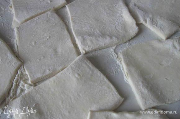 Тесто разморозить, раскатать в более тонкий пласт. Разрезать на прямоугольные кусочки. Положить кусочки теста на противень, застеленный бумагой для выпечки.