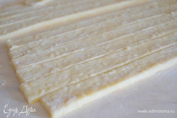 Тесто раскатать на столе, обильно присыпанном мукой. Нарезать на одинаковые полоски. Посыпать кунжутом по вкусу или травками.