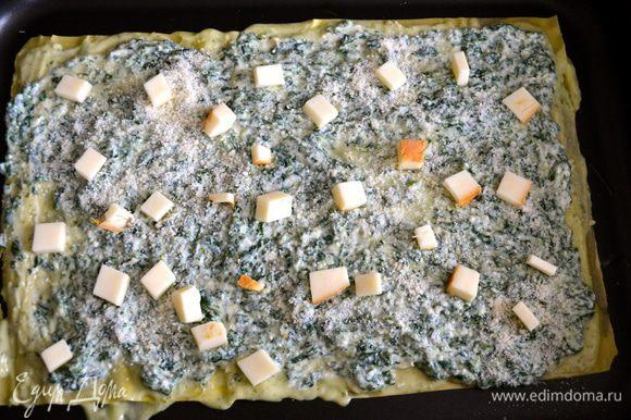 Сверху распределяем крем на рикотте со шпинатом. Присыпаем тертым сыром пармезан и выкладываем кубики копченого сыра.