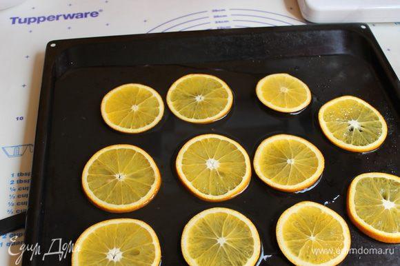 Пока бисквит печется , апельсины нарезаем шириной примерно 0,4мм, кладем кружки на лист посыпаем сахаром (80гр) и поливаем водой смешаной с лимонным соком.