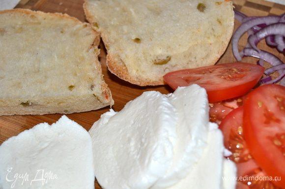 Лук нарезать тонкими полукольцами. Из чиабатты вырезать кружки по размеру помидоров. Помидоры и моцареллу нарезать тонкими кружками.