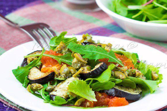 Готовые баклажаны разрезать на половинки. На каждую тарелку выложить горсть листьев, добавить баклажан и несколько томатов. Сверху густо полить получившейся заправкой.