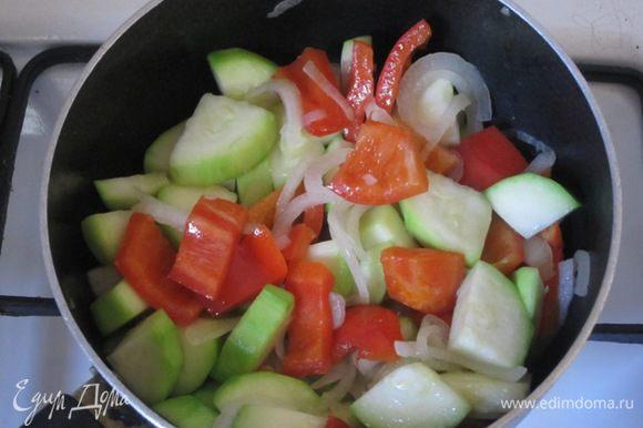 В сотейнике разогреть растительное масло. Выложить перец, кабачок и лук. Обжарить, помешивая, до образования золотистой корочки.