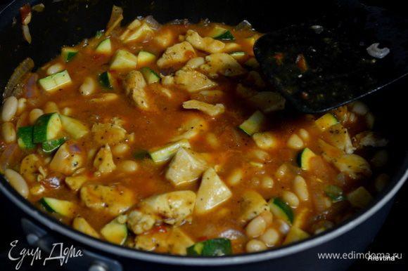 Обжарим лук, чеснок примерно 2-3 мин. Затем добавим цукини, куриные грудки готовые, фасоль из банки (помытую), помидоры и томатный соус. Довести до кипения,огонь убавить, закрыть крышкой и тушить 5 мин. Переложить в жаропрочное блюдо.