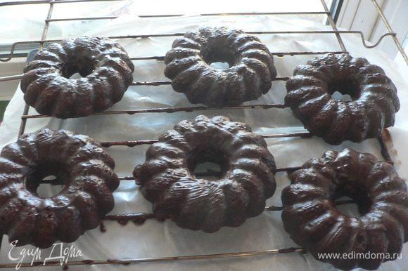 Для шоколадной глазури сложить шоколад в огнеупорную миску, добавить молоко и нарезанное кубиками масло. Поставить на водяную баню и нагревать, пока шоколад и масло не начнут плавиться. Размешать, чтобы получилась однородная масса. Переставить решетку с остывшими кофейными кольцами на противень или большую форму, чтобы собирать стекающую глазурь. Намазать кисточкой шоколадную глазурь на изделия по всей поверхности. Оставить на час.