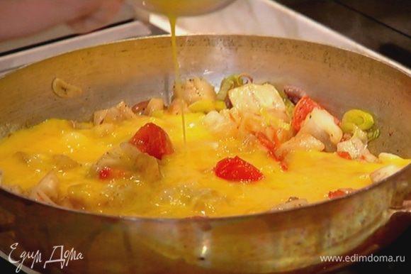 Яйца посолить, поперчить, взбить венчиком, влить в сковороду с овощами и посыпать все натертым сыром. Жарить омлет, слегка помешивая у краев, чтобы он не получился сухим.