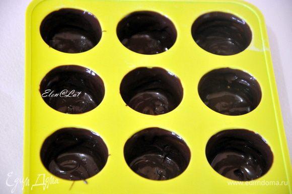 Теперь берем формочки для конфет и с помощью плоской кисточки наносим шоколад по бокам и дно будущей конфетки. Отправляем в холодильник на 10 минут. Затем опять повторяем манипуляцию смазывания стенок и дна. И снова в холодильник на 5 минут.