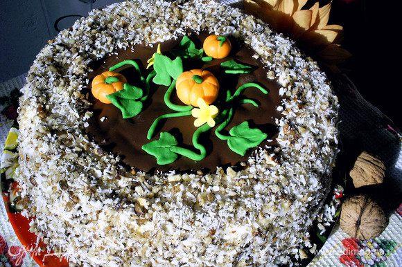 На средину торта выкладываем застывший шоколадный диск. Сверху выкладываем тыковки, цветочки и листву, формируя кустик. Оставшееся пространство засыпаем посыпкой. Отправляем торт на несколько часов в холодильник. Приятного аппетита!