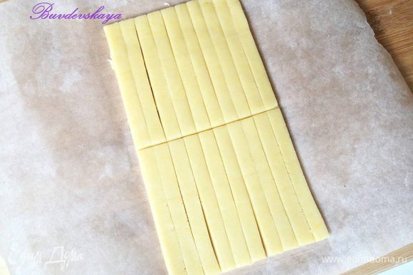 Достать тесто из холодильника, разрезать на 2 части и вторую часть убрать обратно в холодильник, так как лучше работать с холодным тестом. Раскатать тесто толщиной примерно в 1 см, нарезать при помощи линейки на полоски длиной 20 см и шириной 1 см. Затем разрезать полоски на пополам, чтобы получились палочки длиной 10 см.