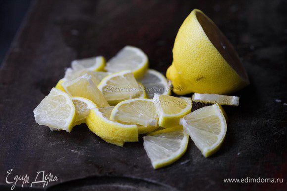 Лимон помыть, половину нарезать на четвертинки.