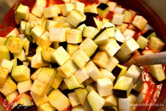После того, как томат прокипит 15 минут, положить в него нарезанные баклажаны и дать покипеть 10 минут.