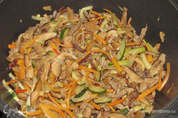 Ранее нарезанные морковь и цукини соединить с мясом и грибами, добавить сухой имбирь, мелко нарезанный зеленый острый перец, посолить. Все хорошо перемешать и быстро обжарить при постоянном помешивании. Овощи не должны стать мягкими, они должны остаться слегка хрустящими и сочными. В конце жарки добавить рисовый уксус, перемешать. Снять с огня, накрыть крышкой.