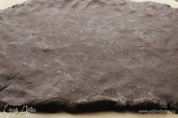 Выложить тесто на выстеленную пергаментом поверхность и раскатать пласт размером примерно 25 / 30 см.