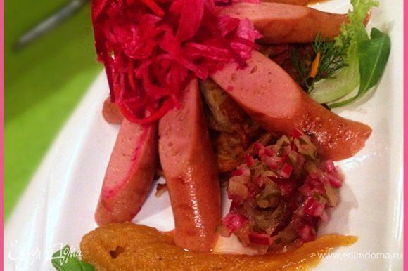Сначала выкладываем на тарелку теплые лепешки из кабачков, по кругу выкладываем дольки сосисок, сверху выкладываем квашеную капусту с перемешанной мелко порезанной свежей свеклой. Заправку из лука и огурца выкладываем с одной стороны блюда, а яблочно-морковное пюре с другой.