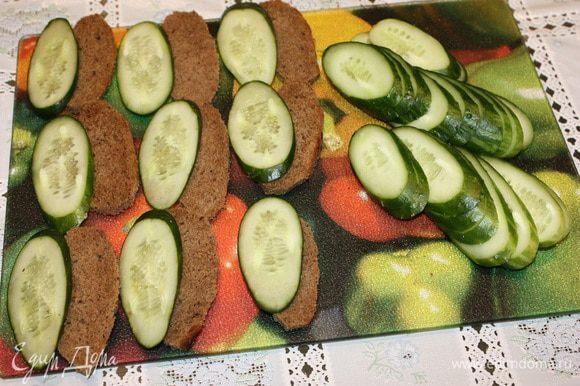 Хлеб и огурцы порезать одинаковой формы. Яйца сварить, почистить и разрезать на четыре части.