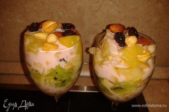 Десерт для взрослых - в фужере фрукты слоями, добавьте йогурт, орешки и изюм.