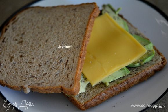 Хлеб можно обжарить на тостере предварительно. Выложить авокадо дольками, посолить и поперчить, затем сыр пластинками. Поставим в микроволновку на 30 секунд.