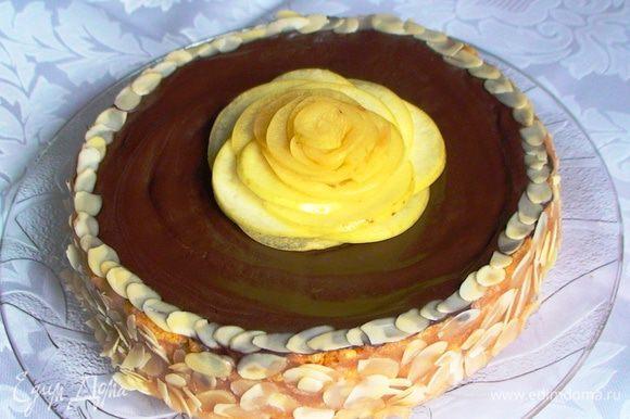 Промазать все коржи кремом (кроме верхнего), складывая их друг на друга. Бока торта тоже обмазать кремом и обсыпать миндальными хлопьями. Украсить торт растопленным с растительным маслом и немного остывшим шоколадом, миндальными хлопьями и розой из яблока.