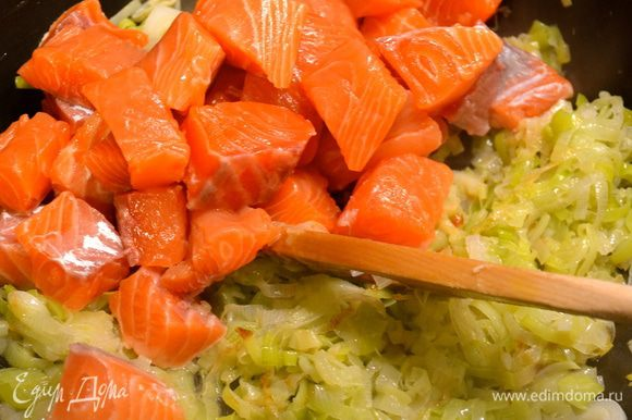 Филе семги очистить от кожи и нарезать небольшими кубиками. По истечении указанного времени добавить кусочки рыбы к луку. Обжарить пару минут на сильном огне, добавить белое вино и дать ему испариться.