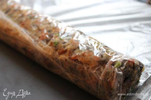 На доску натянуть пищевую плёнку. Выложить на плёнку начинку и сформировать колбаску, на 2-3 см меньшую, чем длина куска мяса. Завернуть колбаску в плёнку и убрать в морозильник на ночь.