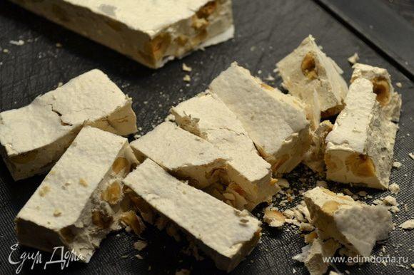 Так выглядит традиционное итальянское рождественское лакомство c орехами, пастила - Torrone. За два часа до начала приготовления десерта убрать пастилу в морозилку. Затем достать и нарезать ее кусочками.