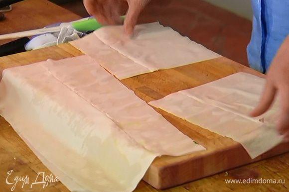 Пласт теста фило смазать растопленным сливочным маслом, сверху положить второй пласт теста и разрезать на 4 квадрата.