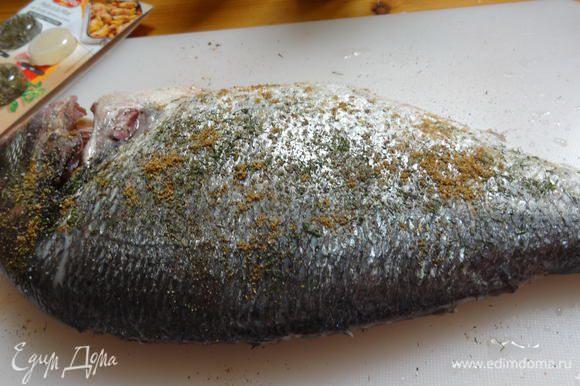 Натереть дораду изнутри и снаружи морской солью, смесью перцев и кориандром.