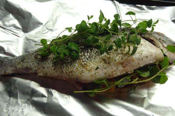 Выложить дораду на пищевую фольгу. Сверху положить орегано веточками. Завернуть рыбу в фольгу и поставить выпекаться в разогретую до 200° С духовку на 30-35 минут.