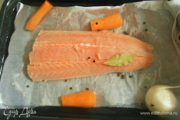 Положите филе в противень кожей вниз, залейте холодной водой так, чтобы только покрыть рыбу. Поставьте на сильный огонь, сразу на 2 конфорки. Добавьте разрезанную морковь, лук, перец горошком, лавровый лист и соль.