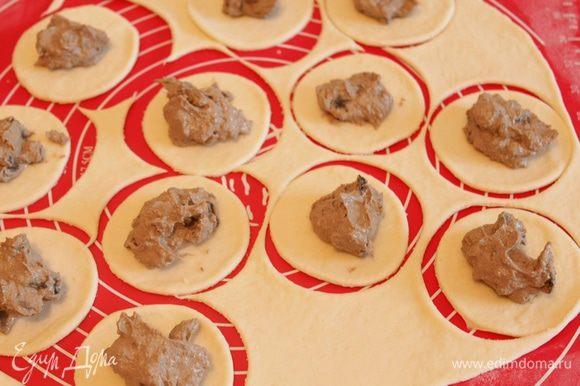 Тесто тонко раскатать, вырезать стаканом кружки. На каждый кружок выложить чайную ложку начинки и сформировать пирожки.