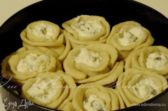 Затем получившиеся розочки выкладываю в форму для выпечки, предварительно смазанную маслом. Смазываю поверхность пирога взбитым желтком и присыпаю кунжутом.