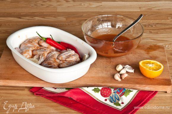 После маринования, смахнуть с цыпленка остатки маринада. Уложить на противень застеленный пергаментом. Вместе с перцем и разрезанным пополам чесноком.
