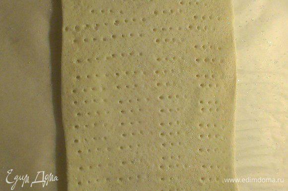 Наколите вилкой тесто, смажьте желтком и отправьте его в разогретую до 200° С духовку до момента, когда поверхность станет золотистой.